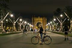 Η νέα και ελκυστική γυναίκα στο ποδήλατο στέκεται μπροστά από Arc de Triomf Στοκ Εικόνες