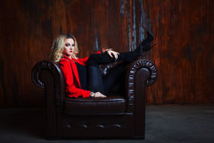 Η νέα και ελκυστική ξανθή γυναίκα στο κόκκινο σακάκι κάθεται στην πολυθρόνα δέρματος, πόδια armrest Στοκ εικόνες με δικαίωμα ελεύθερης χρήσης