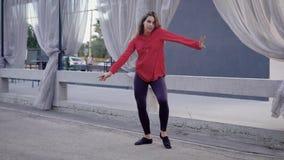 Η νέα και λεπτή γυναίκα χορευτών οδών πηδά και σε μια οδό στην ημέρα, που χορεύει στο φράκτη φιλμ μικρού μήκους