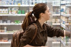 Η νέα και όμορφη γυναίκα παίρνει το απαραίτητο προϊόν από το ψυγείο στο γαλακτοκομικό τμήμα o στοκ εικόνα
