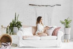Η νέα και όμορφη ξανθή πρότυπη γυναίκα με το τέλειο σώμα στο μοντέρνο εσώρουχο σατέν κάθεται στον καναπέ και την ανάγνωση α στοκ φωτογραφία