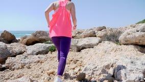 Η νέα κατάλληλη γυναίκα τρέχει το δύσκολο ίχνος κατά μήκος της παραλίας Ίχνος που οργανώνεται στους βράχους o Πίσω πυροβολισμός απόθεμα βίντεο