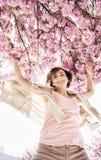Η νέα καυκάσια γυναίκα πηδά κάτω από το ανθίζοντας δέντρο sakura Στοκ φωτογραφίες με δικαίωμα ελεύθερης χρήσης