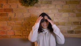 Η νέα καυκάσια γυναίκα brunette στα τρισδιάστατα γυαλιά προσέχει τη ταινία τρόμου και ξαπλώνει στον καναπέ στη τρομακτική απροσδό φιλμ μικρού μήκους