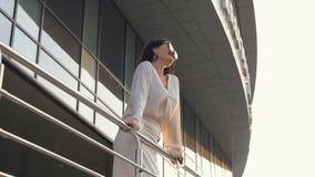 Η νέα καυκάσια επιχειρησιακή γυναίκα κρατά επάνω στο κιγκλίδωμα και εξετάζει έξω την πόλη στο ηλιοβασίλεμα Το κορίτσι Brunette απ φιλμ μικρού μήκους