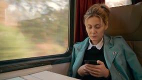 Η νέα καυκάσια επιχειρησιακή γυναίκα ταξιδεύει σε μια intercity μεταφορά τραίνων πολυτέλειας Χρησιμοποιεί ένα κινητό τηλέφωνο Επι απόθεμα βίντεο