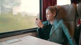 Η νέα καυκάσια επιχειρησιακή γυναίκα ταξιδεύει σε μια intercity μεταφορά τραίνων πολυτέλειας Χρησιμοποιεί ένα κινητό τηλέφωνο για απόθεμα βίντεο