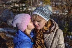 Η νέα καυκάσια μητέρα ακούει η κόρη μικρών παιδιών της που ψιθυρίζει με το χαμόγελο Στοκ φωτογραφία με δικαίωμα ελεύθερης χρήσης