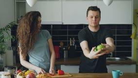 Η νέα καυκάσια σγουρή όμορφη γυναίκα που κόβει τη prepearing σαλάτα κόκκινων πιπεριών, ο σύζυγός της έρχεται, φιλώντας την, που π φιλμ μικρού μήκους