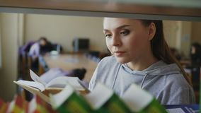 Η νέα καυκάσια όμορφη γυναίκα σπουδαστής στέκεται κοντά στο ράφι με τα βιβλία στη μεγάλη ευρύχωρη εκμετάλλευση βιβλιοθηκών ένα, σ απόθεμα βίντεο