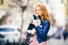 Η νέα κοκκινομάλλης καυκάσια γυναίκα με τις φακίδες στο πρόσωπο κρατά και φιλά, αγκαλιάζει, αγαπά το γραπτό δασύτριχο σκυλί της φ στοκ εικόνα