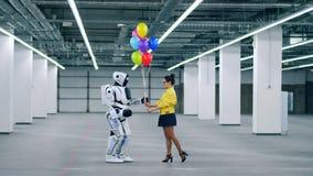 Η νέα κυρία δίνει τα ζωηρόχρωμα μπαλόνια σε ένα ρομπότ απόθεμα βίντεο