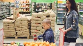 Η νέα κυρία και ο γιος της στα σακάκια τζιν ψωνίζουν μαζί, περπατούν μέσω του διαδρόμου στο κοίταγμα υπεραγορών απόθεμα βίντεο