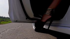 Η νέα κυρία παίρνει από το αυτοκίνητο Γυναίκα που βγαίνει το αυτοκίνητο Κλείστε επάνω στην πόρτα αυτοκινήτων και το πόδι κοριτσιώ φιλμ μικρού μήκους