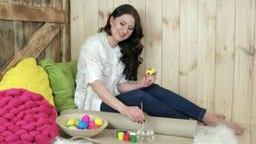 Η νέα κυρία παρουσιάζει ψάθινο σύνολο πιάτων των ζωηρόχρωμων αυγών, πορτρέτο, διακοσμημένο αυγό Πάσχας απόθεμα βίντεο