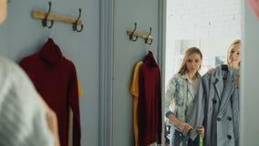 Η νέα κυρία στα περιστασιακά ενδύματα δοκιμάζει το παλτό στην εγκατάσταση του δωματίου και την ερώτηση του φίλου της για τις συμβ φιλμ μικρού μήκους