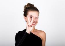 Η νέα κυρία φωτογραφιών μόδας κινηματογραφήσεων σε πρώτο πλάνο στο κομψό μαύρο φόρεμα, εύθυμο χαμόγελο γυναικών και παρουσιάζει έ Στοκ εικόνες με δικαίωμα ελεύθερης χρήσης