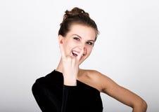Η νέα κυρία φωτογραφιών μόδας κινηματογραφήσεων σε πρώτο πλάνο στο κομψό μαύρο φόρεμα, εύθυμο χαμόγελο γυναικών και παρουσιάζει έ Στοκ Φωτογραφίες