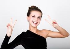 Η νέα κυρία φωτογραφιών μόδας κινηματογραφήσεων σε πρώτο πλάνο στο κομψό μαύρο φόρεμα, εύθυμο χαμόγελο γυναικών και παρουσιάζει έ Στοκ Εικόνα