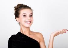 Η νέα κυρία φωτογραφιών μόδας κινηματογραφήσεων σε πρώτο πλάνο στο κομψό μαύρο φόρεμα, εύθυμο χαμόγελο γυναικών και παρουσιάζει χ Στοκ Φωτογραφία