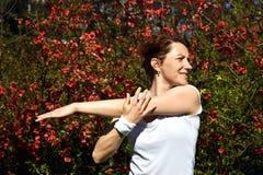 Η νέα κόκκινη κυρία τρίχας τεντώνει το βραχίονά της μετά από την υπαίθρια κατάρτιση στο πάρκο στοκ εικόνες