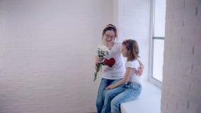Η νέα κόρη δίνει τα λουλούδια, το αγκάλιασμα και την αγάπη μητέρων Οικογενειακός τρόπος ζωής αγάπης απόθεμα βίντεο
