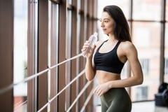 Η νέα λεπτή γυναίκα ικανότητας πίνει το νερό μετά από τις ασκήσεις γιόγκας στο στούντιο γιόγκας στοκ εικόνα