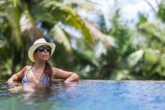 Η νέα λεπτή γυναίκα brunette κάνει ηλιοθεραπεία στην τροπική πισίνα στοκ εικόνα
