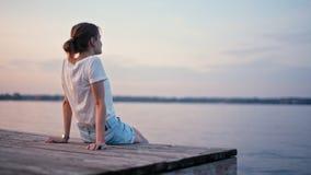 Η νέα λεπτή κυρία απολαμβάνει την πυράκτωση θερινού ηλιοβασιλέματος κοντά στη λίμνη και τη χαλάρωση φιλμ μικρού μήκους