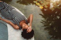 Η νέα μαύρη έγκυος γυναίκα βάζει κοντά σε μια τροπική λίμνη στοκ εικόνες με δικαίωμα ελεύθερης χρήσης