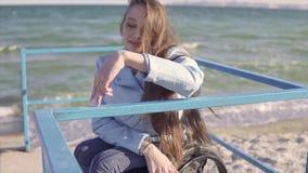 Η νέα με ειδικές ανάγκες γυναίκα στην αναπηρική καρέκλα παρουσιάζει βήμα δάχτυλων περπατώντας από τα κιγκλιδώματα στην κεκλιμένη  απόθεμα βίντεο