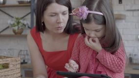Η νέα μητέρα έβαλε στο επιτραπέζιο κιβώτιο με το ψωμί και την ομιλία στη μικρή κόρη της που παίζει τα παιχνίδια στην ταμπλέτα απόθεμα βίντεο