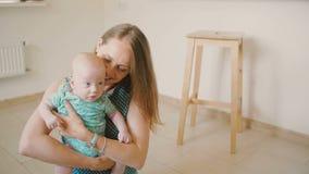 Η νέα μητέρα ανυψώνει επάνω το πολύτιμο μωρό της, που μιλά σε τον με ένα χαμόγελο καθμένος στο πάτωμα κουζινών σε αργή κίνηση απόθεμα βίντεο