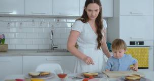Η νέα μητέρα βοηθά ένα παιδί για να μαγειρεψει τα burgers στην κουζίνα φιλμ μικρού μήκους