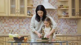 Η νέα μητέρα διδάσκει τη λατρευτή κόρη της για να κόψει τα αγγούρια για τη σαλάτα απόθεμα βίντεο
