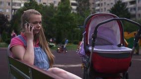 Η νέα μητέρα κάθεται στον πάγκο στην παιδική χαρά, μιλά για να τηλεφωνήσει Κόκκινη μεταφορά μωρών απόθεμα βίντεο