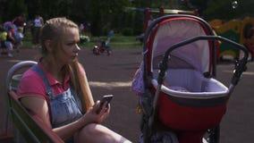 Η νέα μητέρα κάθεται στον πάγκο στην παιδική χαρά, που τρυπά στο smartphone Μεταφορά μωρών απόθεμα βίντεο