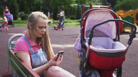 Η νέα μητέρα κάθεται στον πάγκο στη βρύση παιδικών χαρών στο smartphone Μεταφορά μωρών Καλοκαίρι απόθεμα βίντεο