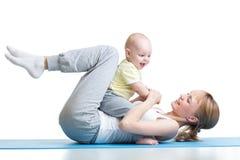 Η νέα μητέρα και το μωρό κάνουν την άσκηση και έχουν τη διασκέδαση σε ένα άσπρο υπόβαθρο Στοκ φωτογραφίες με δικαίωμα ελεύθερης χρήσης