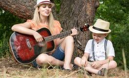 Η νέα μητέρα και το όμορφο υπόλοιπο γιων στο δάσος, τραγουδούν τα τραγούδια κάτω από μια κιθάρα στοκ εικόνα