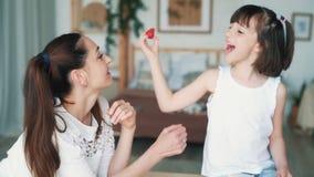 Η νέα μητέρα και χαριτωμένος λίγη κόρη τρώει τις φράουλες, σε αργή κίνηση απόθεμα βίντεο
