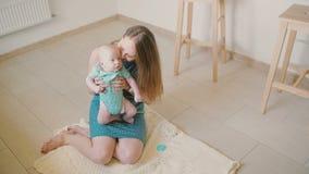 Η νέα μητέρα κρατά το πολύτιμο μωρό της, χαμογελά σε τον και γελά καθμένος στο πάτωμα κουζινών κίνηση αργή απόθεμα βίντεο