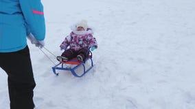 Η νέα μητέρα κυλά λίγο μωρό στο έλκηθρο κατά μήκος του χιονώδους δρόμου το χειμώνα Το παιδί είναι άτακτο και φωνάζει καθμένος στο φιλμ μικρού μήκους