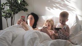 Η νέα μητέρα, η κόρη και λίγος γιος χρησιμοποιούν τις συσκευές σε ένα άσπρο κρεβάτι Σύγχρονη οικογένεια έννοιας κατά τη διάρκεια  απόθεμα βίντεο