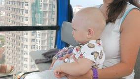 Η νέα μητέρα με ένα όμορφο μωρό αναρριχείται πέρα από την πόλη με το τελεφερίκ Το παιδί κοιτάζει επίμονα στις πλευρές απόθεμα βίντεο