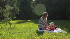 Η νέα μητέρα με την κόρη νηπίων της κάθεται στο άσπρο κάλυμμα στον πράσινο χορτοτάπητα άνοιξη απόθεμα βίντεο