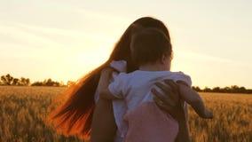 Η νέα μητέρα με την λίγη κόρη χορεύει και γελά στον τομέα του σίτου, στις ακτίνες ενός όμορφου ηλιοβασιλέματος αργός απόθεμα βίντεο