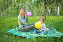 Η νέα μητέρα με τη διασκεδάζοντας κόρη της διογκώνει το ζωηρόχρωμο μπαλόνι Στοκ φωτογραφία με δικαίωμα ελεύθερης χρήσης
