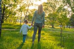 Η νέα μητέρα με τη διασκεδάζοντας κόρη της περπατά μέσω του πάρκου Στοκ Εικόνες