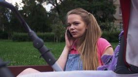 Η νέα μητέρα μιλά για να τηλεφωνήσει στον πάγκο Μεταφορά μωρών δέντρο πεδίων Χαμόγελο απόθεμα βίντεο